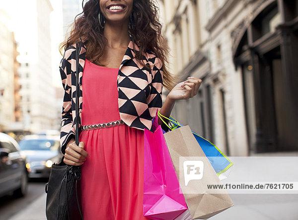 Frau trägt Einkaufstaschen auf der Stadtstraße