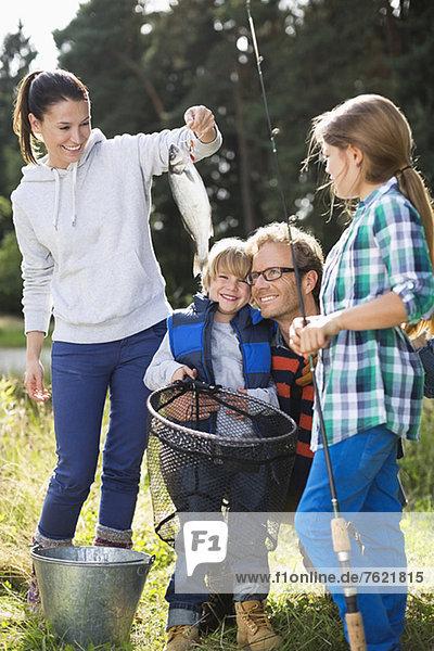 Familie  die den Fischfang bewundert Familie, die den Fischfang bewundert