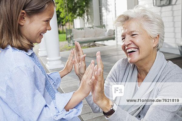 Frau und Enkelin beim Klatschspiel Frau und Enkelin beim Klatschspiel