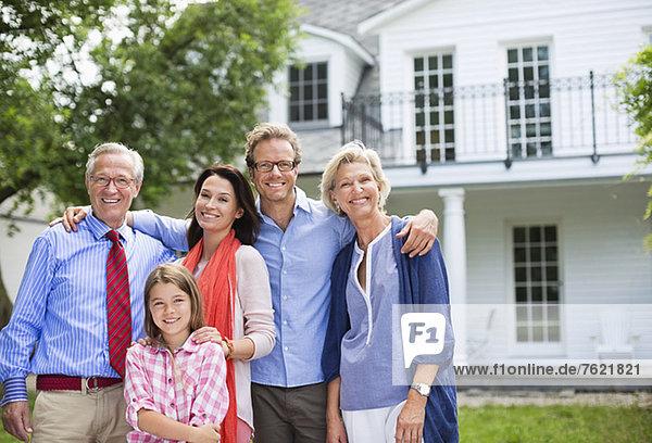 Familie lächelt gemeinsam vor dem Haus Familie lächelt gemeinsam vor dem Haus