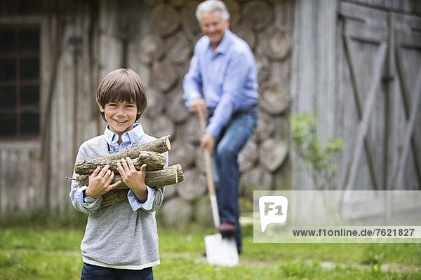 Boy carrying pile of firewood outdoors