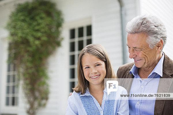 Mann und Enkelin lächeln im Freien Mann und Enkelin lächeln im Freien