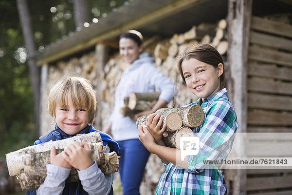 Kinder mit Brennholz im Freien Kinder mit Brennholz im Freien