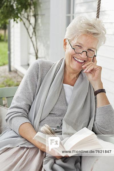Frau liest Buch auf Veranda-Schaukel Frau liest Buch auf Veranda-Schaukel