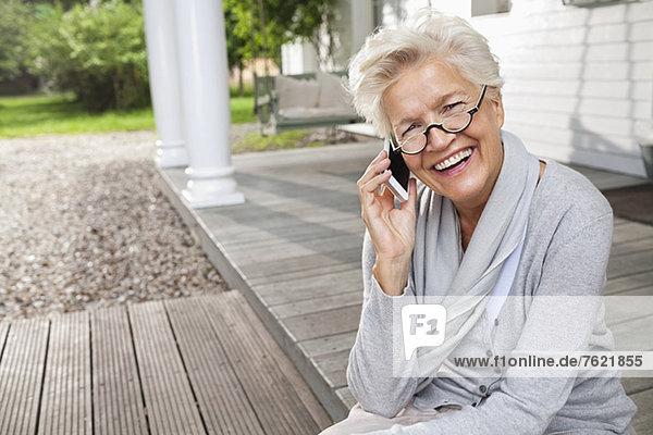 Frau spricht auf dem Handy auf der Veranda Frau spricht auf dem Handy auf der Veranda