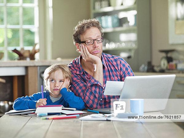 Gelangweilter Vater und Sohn bei der Arbeit am Tisch Gelangweilter Vater und Sohn bei der Arbeit am Tisch