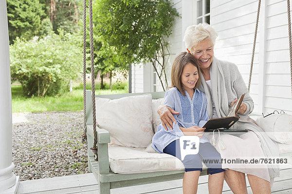 Frau und Enkelin beim Lesen auf der Veranda-Schaukel Frau und Enkelin beim Lesen auf der Veranda-Schaukel