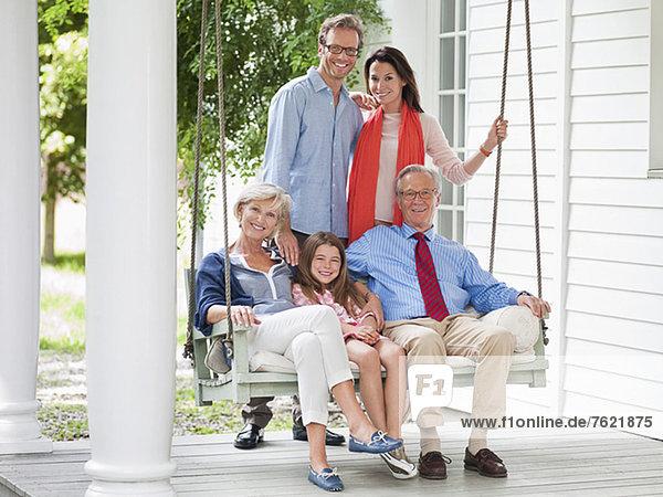 Familie lächelt gemeinsam auf der Veranda Familie lächelt gemeinsam auf der Veranda
