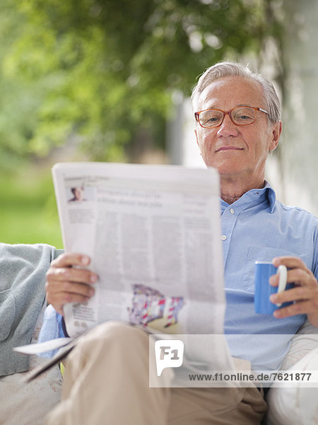 Mann liest Zeitung in Veranda-Schaukel Mann liest Zeitung in Veranda-Schaukel