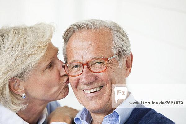 Lächelnde Frau küssend Ehemann Lächelnde Frau küssend Ehemann