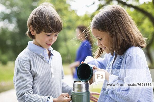 Kinder beim Ausgießen von Tee aus der Thermoskanne im Freien Kinder beim Ausgießen von Tee aus der Thermoskanne im Freien