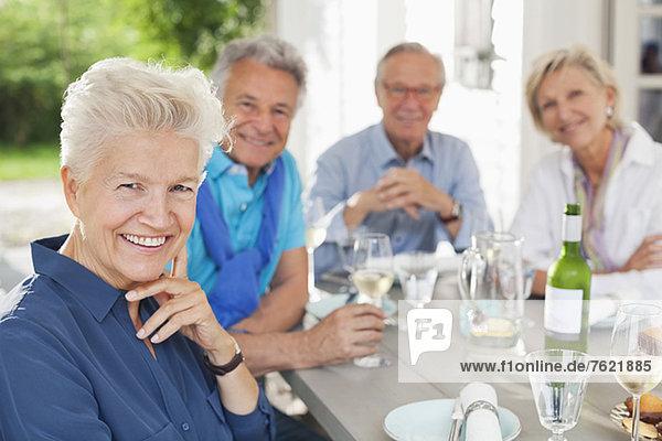 Freunde lächeln bei Tisch im Freien Freunde lächeln bei Tisch im Freien