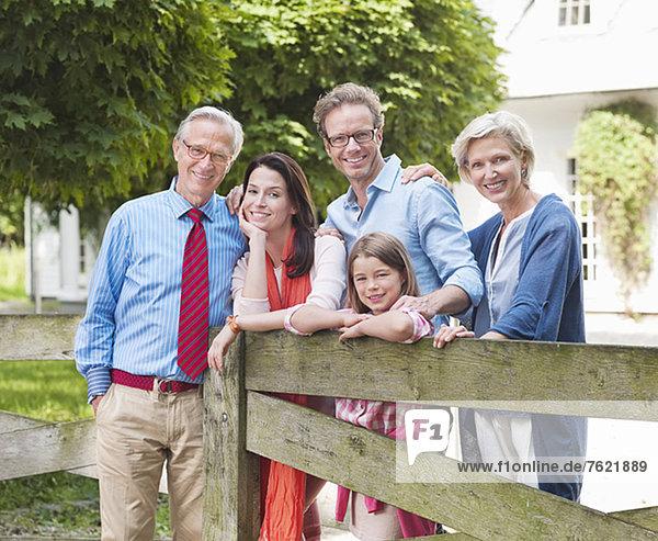 Familie lächelt zusammen durch Holzzaun Familie lächelt zusammen durch Holzzaun
