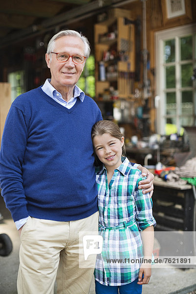 Mann und Enkelin lächeln in der Garage Mann und Enkelin lächeln in der Garage