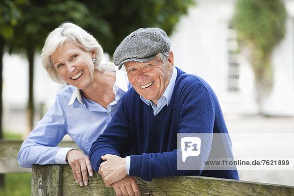 Paar lächelnd durch Holzzaun Paar lächelnd durch Holzzaun