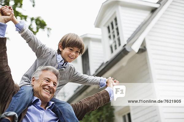 Mann mit Enkel auf den Schultern im Freien Mann mit Enkel auf den Schultern im Freien