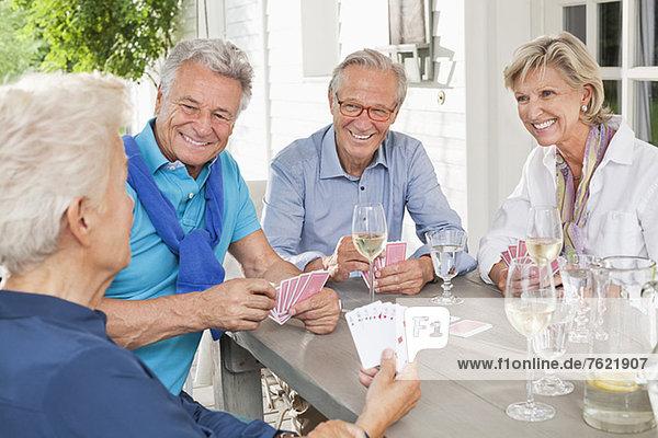 Freunde spielen Kartenspiele am Tisch Freunde spielen Kartenspiele am Tisch