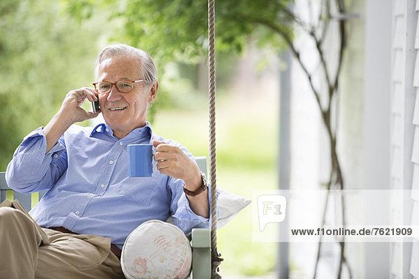 Mann spricht auf dem Handy in der Veranda Schaukel Mann spricht auf dem Handy in der Veranda Schaukel