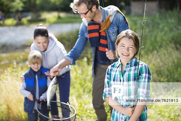 Familie  die den Fischfang im Freien bewundert Familie, die den Fischfang im Freien bewundert