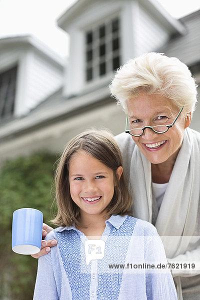 Frau und Enkelin lächeln gemeinsam im Freien Frau und Enkelin lächeln gemeinsam im Freien