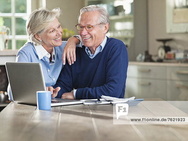 Paar mit Laptop am Küchentisch