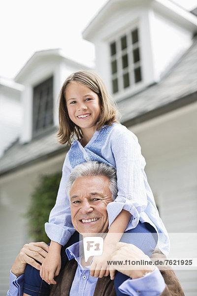 Mann mit Enkelin auf der Schulter im Freien Mann mit Enkelin auf der Schulter im Freien