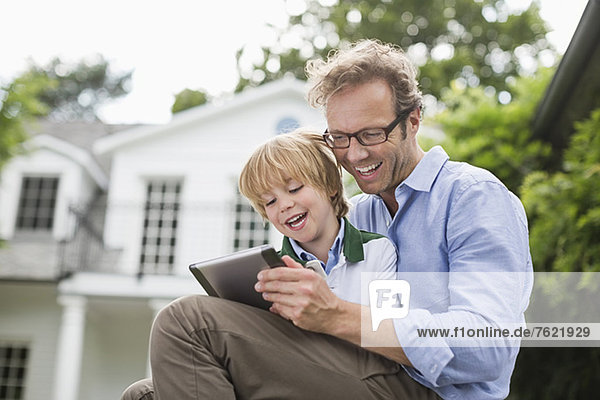 Vater und Sohn nutzen das digitale Tablett im Freien Vater und Sohn nutzen das digitale Tablett im Freien