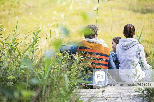 Familienangeln zusammen auf einem Holzsteg Familienangeln zusammen auf einem Holzsteg