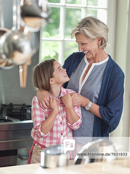 Frau und Enkelin lächeln in der Küche Frau und Enkelin lächeln in der Küche