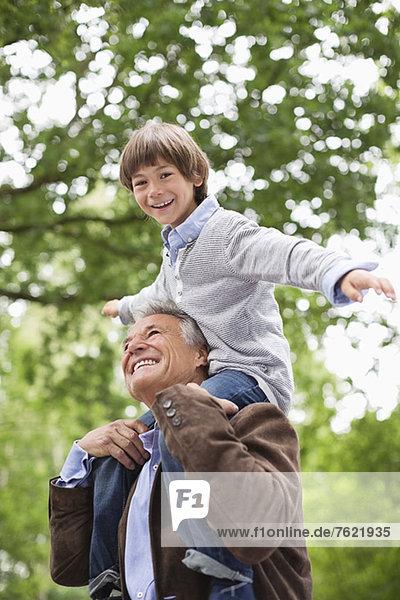Mann mit Enkel auf den Schultern im Freien