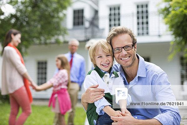 Vater und Sohn lächeln vor dem Haus Vater und Sohn lächeln vor dem Haus