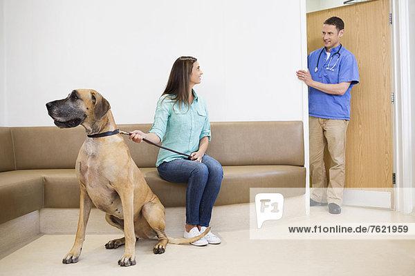 Tierarzt ruft Besitzer und Hund in die Tierarztpraxis