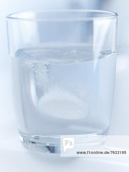 Nahaufnahme der Pille zischend im Glas Wasser
