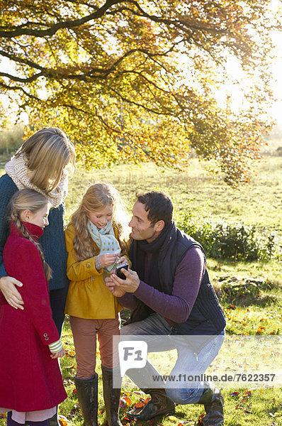 Familie  die gemeinsam im Freien telefoniert