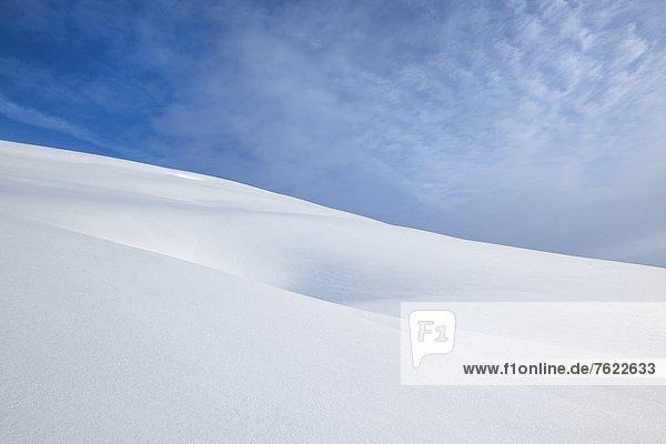 Einbuchtung im Schnee und Himmel mit Wolken am Trattberg  Österreich