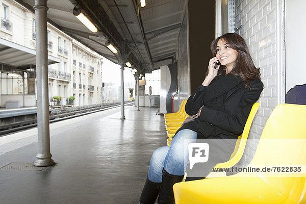 Frau auf dem Handy am Bahnhof