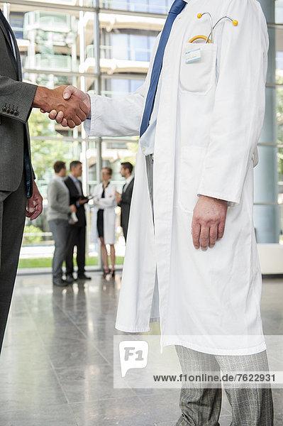 Geschäftsmann und Arzt beim Händeschütteln