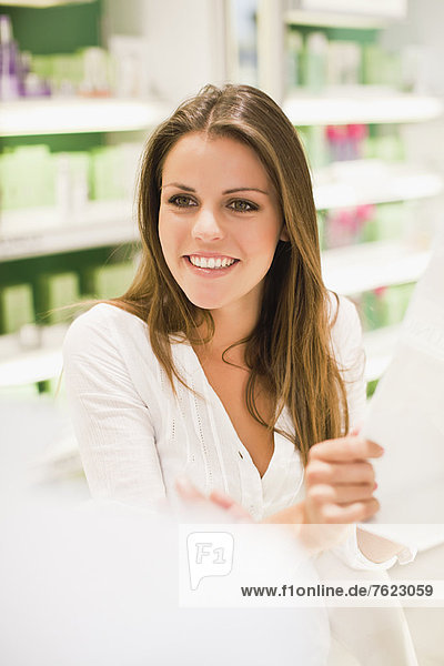 Woman reading paper in store