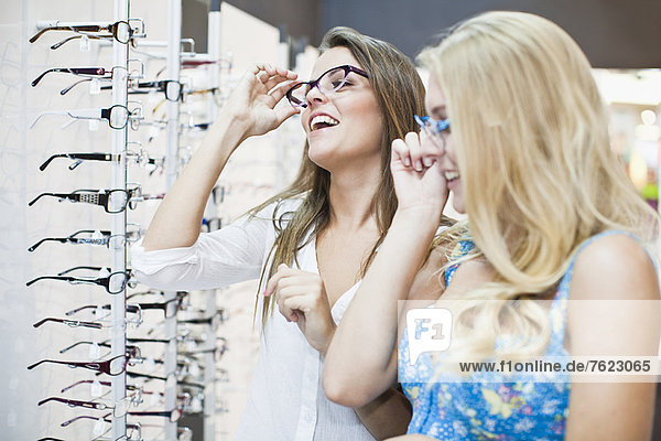 Women trying on glasses in store