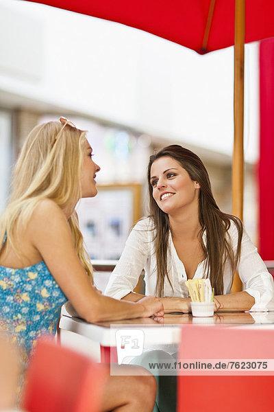 Frauen reden im Straßencafé