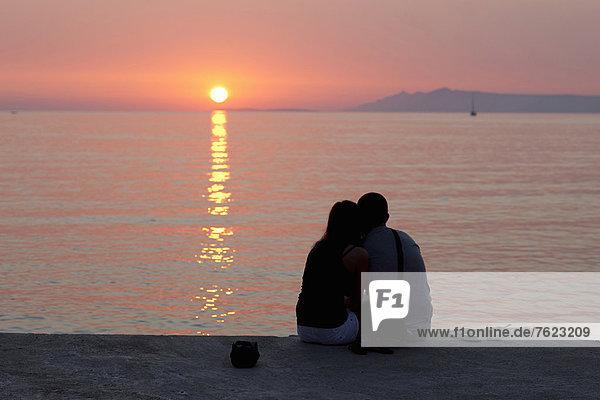 Pärchen beim Sonnenuntergang am Pier entspannen