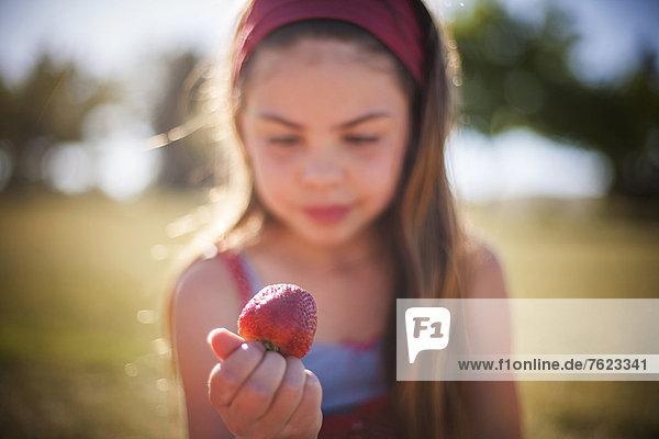 Mädchen essen Erdbeere im Freien