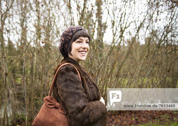 Lächelnde Frau beim Waldspaziergang