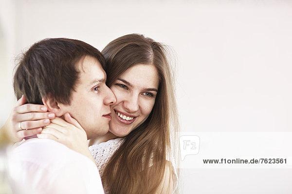 Lächelndes Paar  das sich drinnen umarmt.