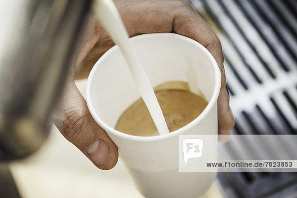 Nahaufnahme des Milchflusses in die Kaffeetasse