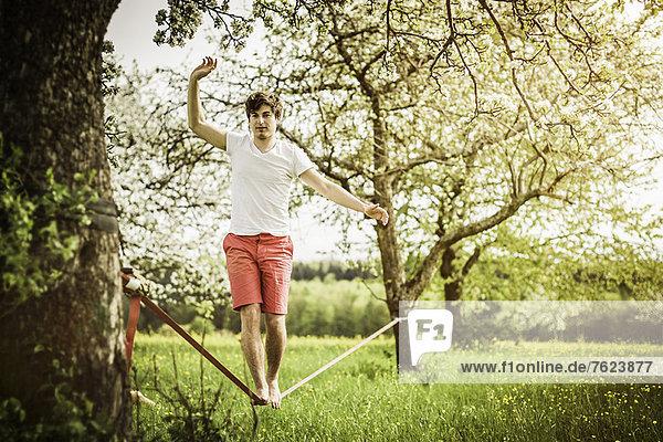 Man walking on tightrope in field