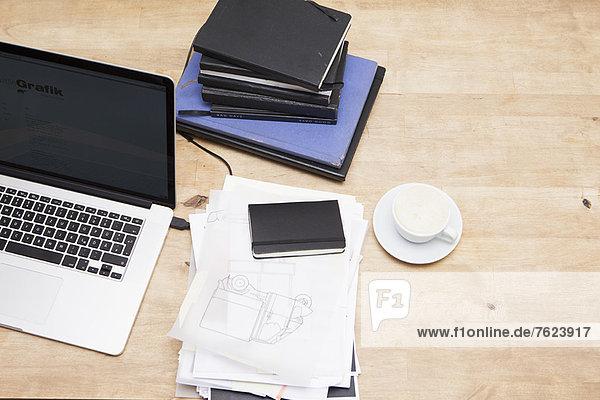 Laptop mit Büchern und Kaffeetasse