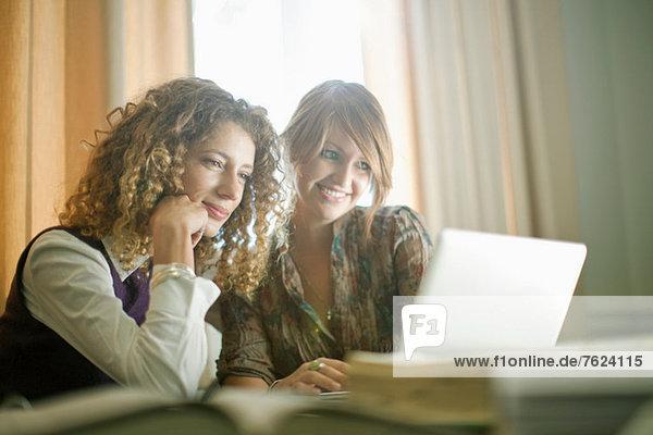 Studenten  die ihren Laptop gemeinsam am Schreibtisch benutzen
