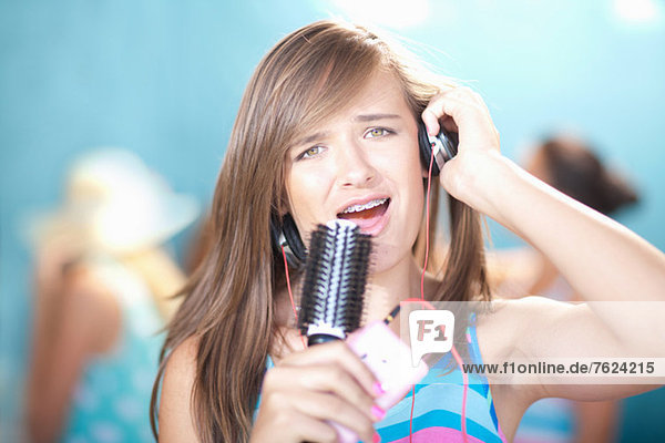 Teenage girl singing into hairbrush