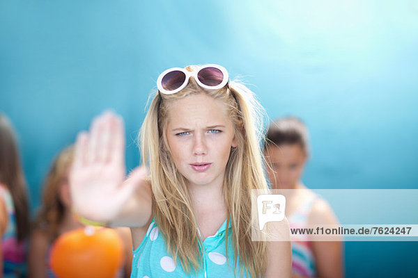 Teenage girl holding hand out to stop